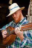 Человек битника при красная борода играя гитару Стоковые Изображения RF