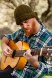 Человек битника при красная борода играя гитару Стоковое фото RF
