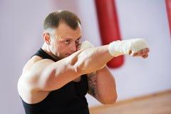 Человек боксера на тренировке бокса с тяжелой сумкой Стоковое Изображение