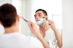 Человек брея бороду с лезвием бритвы на ванной комнате Стоковое фото RF