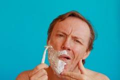 Человек брея его бороду с лезвием бритвы Стоковое Изображение RF