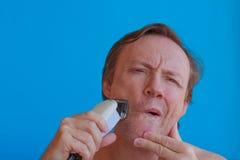 Человек брея его бороду с электробритвой Стоковая Фотография