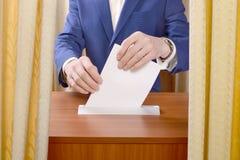 Человек бросает голосование в урну для избирательных бюллетеней Стоковое фото RF