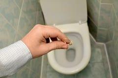 Человек бросает обручальное кольцо в туалет Развод, конец влюбленности стоковая фотография rf