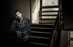 Молодой неудовлетворённый человек сидя на лестницах стоковые изображения