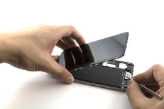 Человек был ремонтником он подготавливает к ремонту мобильного телефона он был лентой запечатывания тяги заменить батарею Стоковые Изображения RF
