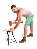 Человек бьет ноготь молотком стоковое изображение
