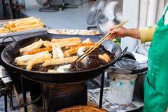 Человек варит youtiao на уличном рынке Стоковые Фото