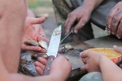 Человек варя мясо над костром на месте для лагеря Стоковое Фото