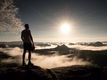 Человек вверху гора смотря туманный ландшафт чувствуйте свободно стоковая фотография rf