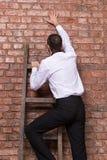 Человек вверх против кирпичной стены стоковые фотографии rf