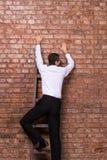 Человек вверх против кирпичной стены стоковое изображение