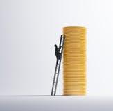 Человек взбираясь куча монеток Стоковая Фотография