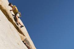 Человек взбираясь на скале стоковое изображение rf