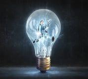 Человек внутри электрической лампочки стоковое изображение