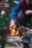 Человек воспламеняет огонь в лесе Стоковые Изображения