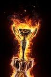 Человек вручает держать горящую чашку трофея золота как победитель Стоковое фото RF