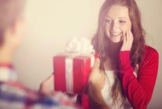 Человек вручая подарок женщины Стоковые Изображения