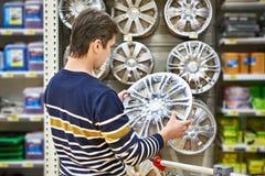 Человек выбирает колеса сплава для автомобиля катит внутри супермаркет Стоковая Фотография RF