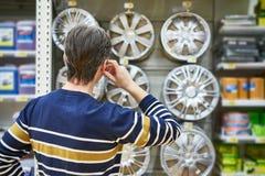 Человек выбирает колеса сплава для вашего автомобиля катит внутри супермаркет Стоковые Изображения