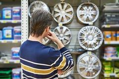 Человек выбирает колеса сплава для вашего автомобиля катит внутри супермаркет Стоковые Изображения RF