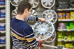 Человек выбирает колеса сплава для вашего автомобиля катит внутри супермаркет Стоковое Изображение RF