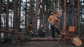 Человек выбирает поднимает сына на руках на барбекю в древесинах и прогулках прочь акции видеоматериалы