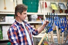 Человек выбирает сено вилы в магазине Стоковые Изображения RF