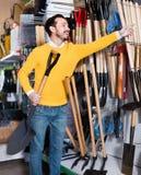 Человек выбирая новый лопаткоулавливатель в магазине оборудования сада Стоковые Фото