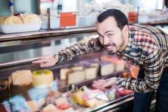Человек выбирая очень вкусный сыр Стоковые Изображения