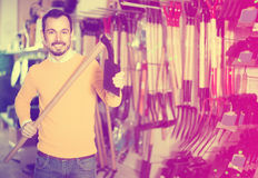 Человек выбирая различные инструменты в магазине оборудования сада Стоковое фото RF