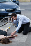Человек вызывая машину скорой помощи для раненой женщины Стоковое Фото
