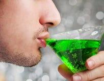 Человек выпивает зеленый коктеиль спирта Стоковое фото RF