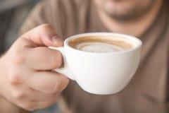 Человек выпивает капучино Стоковое Изображение
