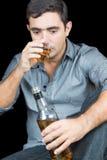 Человек выпивая от бутылки вискиа (изолированной на черноте) Стоковые Фото