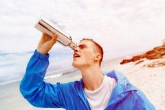 Человек выпивая от бутылки спортов Стоковое Фото
