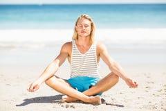 Человек выполняя йогу на пляже Стоковое Фото