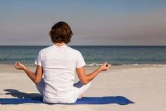 Человек выполняя йогу на пляже Стоковые Фотографии RF