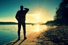 человек высокорослый Заход солнца над островом и причалом на береговой линии Теплые цвета и оттенки восходящего солнца Стоковые Изображения