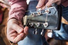 Человек вытягивает гитару новых строк гитары акустическую в крупном плане Стоковые Фото