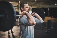 Человек вытягивая вверх по большой штанге в классе фитнеса Стоковые Фотографии RF