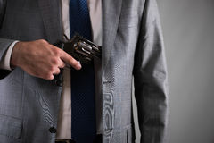 Человек вытягивая вне оружие от его карманн Стоковое Изображение RF