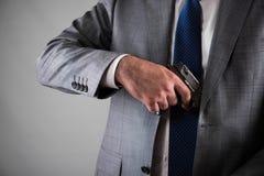 Человек вытягивая вне оружие от его карманн Стоковое Фото
