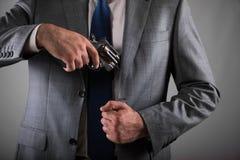Человек вытягивая вне оружие от его карманн Стоковая Фотография