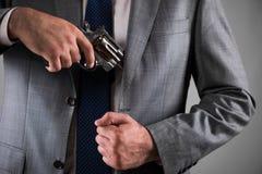 Человек вытягивая вне оружие от его карманн Стоковые Фотографии RF