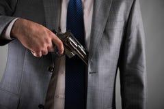 Человек вытягивая вне оружие от его карманн Стоковое Изображение