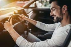 Человек в автосалоне, сидя за колесом Стоковое Изображение
