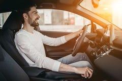 Человек в автосалоне, сидя за колесом Стоковые Изображения