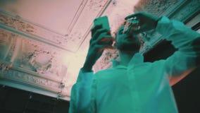 Человек в белой рубашке выпивает alcochol и использование умного телефона на партии ночного клуба акции видеоматериалы