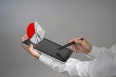 Человек в белой рубашке работая с долевой диограммой на планшете, применением для планирования бюджета или финансовыми статистик Стоковая Фотография RF